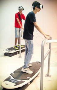 Jovens usam óculos de realidade aumentada 3D, com base em celular em simulador de prancha de surfe. (Foto: George Campos/USP Imagens)