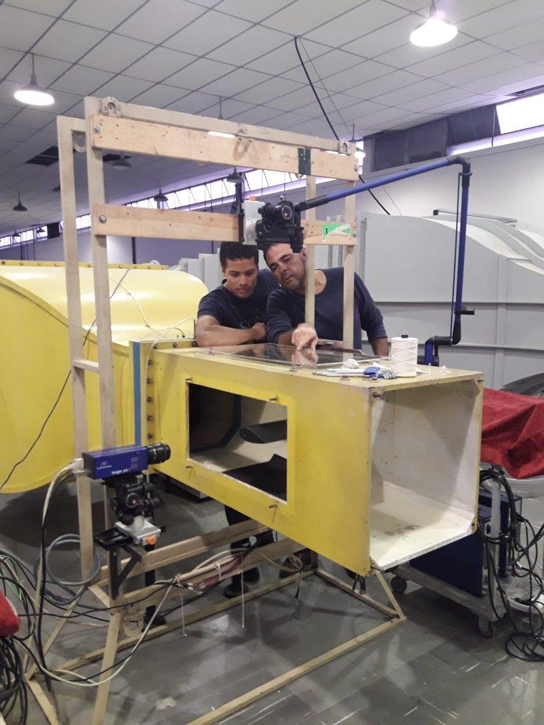 Aluno de Iniciação Científica no ITA, Guilherme Pimentel realiza ensaios em túnel de vento utilizando laser para medição de velocidades do escoamento do ar sobre uma asa com morfologia similar à da baleia jubarte