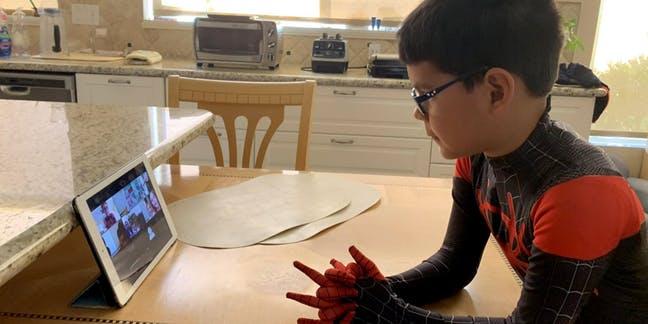 Criança assisti aula online vestido de homem aranha. Crédito: Edsurge