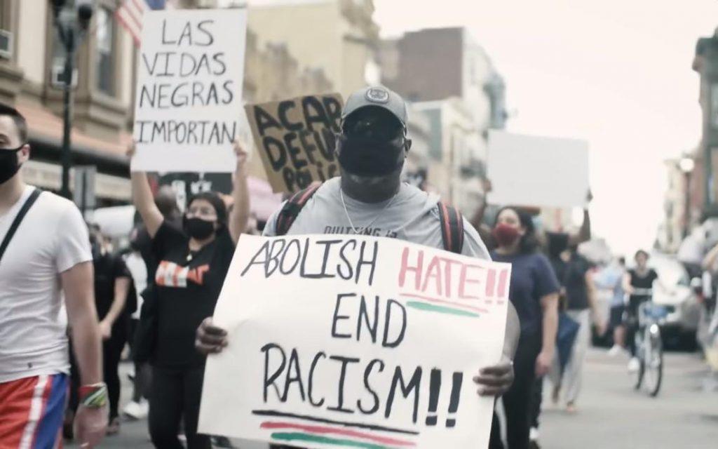 """Cartaz com os dizeres: """"Abolição ao ódio e ao racismo"""". Crédito: NBC News/ Reprodução."""