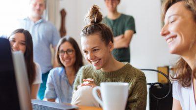 Alunos olhando para um computador e sorrindo