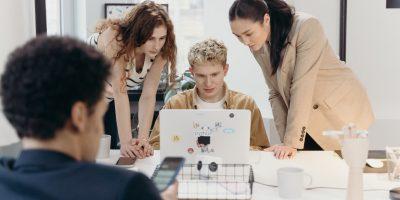 Grupo de jovens conversando com um computador ao redor de uma mesa