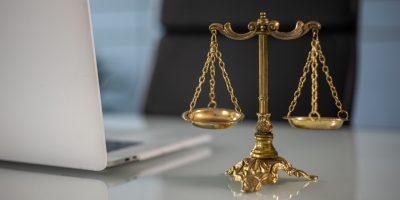 Computador e balança da justiça que representam o curso de direito EaD que pode começar a ser ofertado
