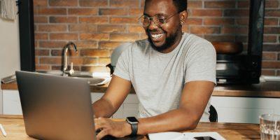 Homem estudando em um computador enquanto sorri